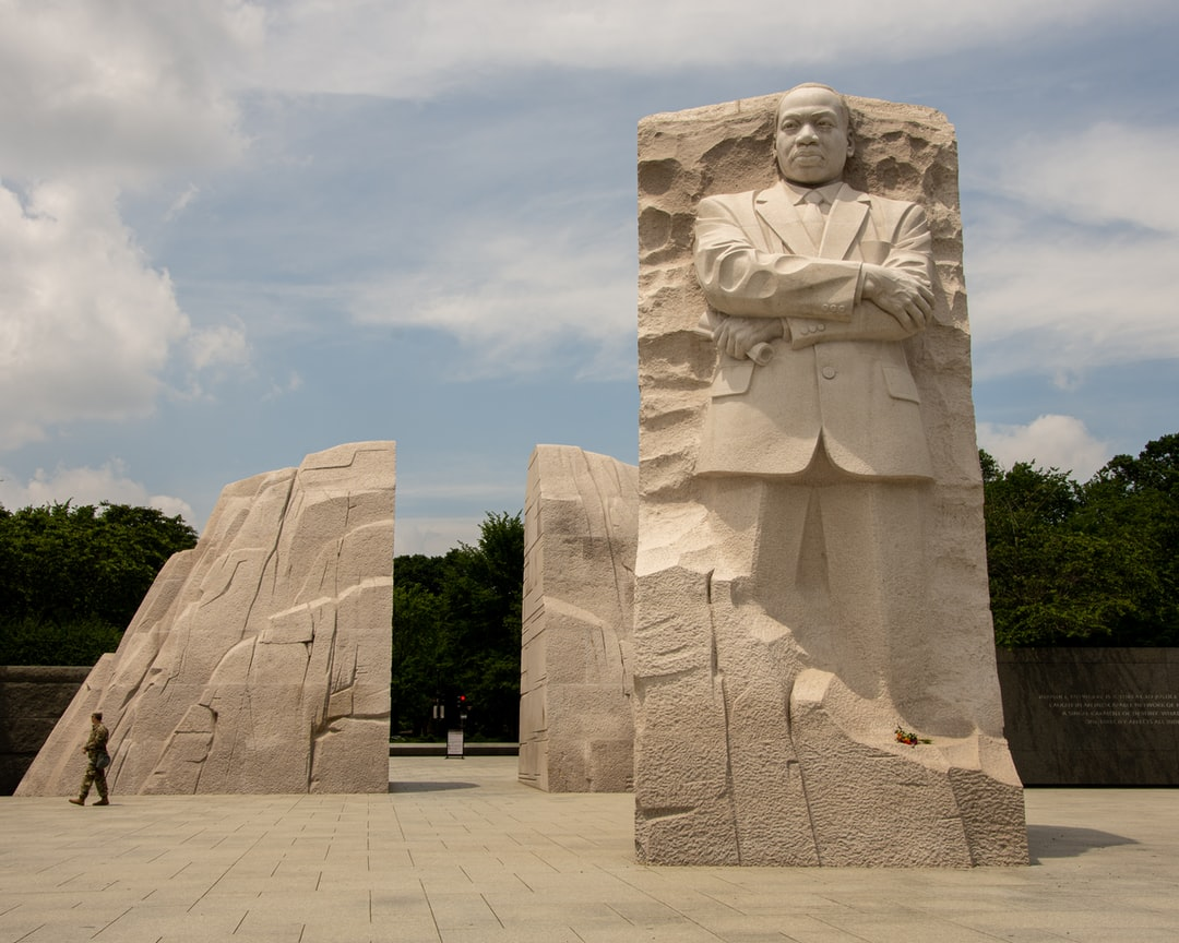 A statue of a stone building with Martin Luther King Jr. Memorial in the background